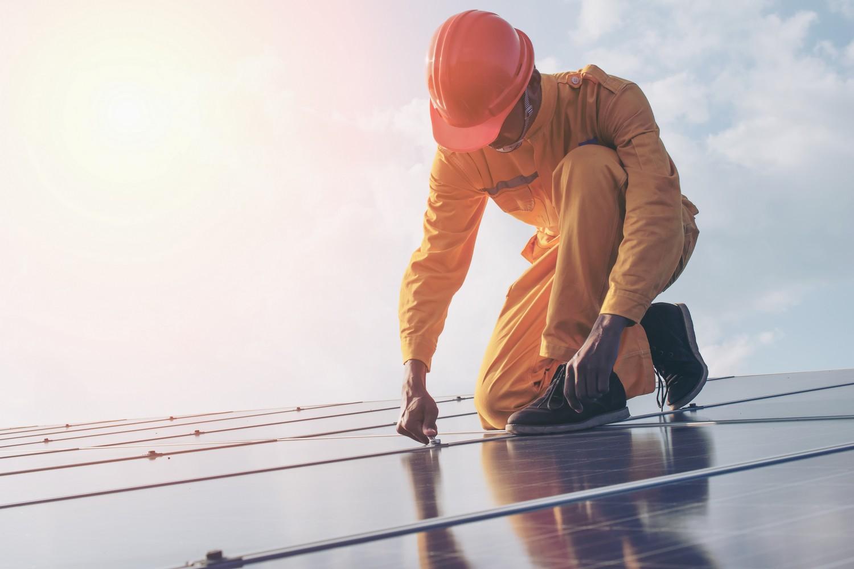 Artisan installant des panneaux solaires.