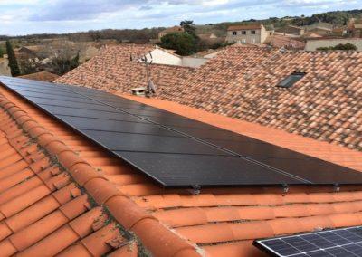 Photo représentant une installation photovoltaïque en autonomie électrique sur une toiture d'un particulier, où l'on peut voir 20 modules SolarWatt 300 posés. Nous voyons que la maison est entourée d'autres habitations mais aussi de nombreux champs, d'arbres et de de sapins, le ciel est également dégagé. Cette installation photovoltaïque en autoconsommation partielle a été réalise par l'installateur solaire Libow à Saint-Marcel-sur-Aude en mars 2019