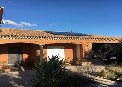 Photo représentant de nombreux panneaux solaires en autonomie partielle sur la toiture d'une maison, notamment 10 panneaux photovoltaïques, tous posés avec la technique en surimposition. Ces modules solaires sont des ALEO. Nous pouvons voir que la maison est entourée au premier plan de nombreuses plantes et palmier mais aussi que le ciel est bien dégagé. Cette installation solaire en autonomie partielle a été réalisé par l'installateur solaire Libow à Montagnac en janvier 2019.