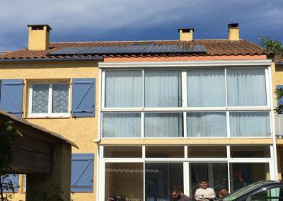 Photo représentant une installation photovoltaïque en autoconsommation sur une toiture de maison d'un particulier, où l'on peut voir 10 modules installés. Les modules photovoltaïques posés sont des Q.CELLS d'une puissance de 300 Wc chacun. Nous pouvons voir autour de la maison quelques végétations, ainsi qu'un ciel dégagé. Cette installation solaire en autonomie partielle a été réalisée par l'artisan Libow à Serignan en avril 2019.