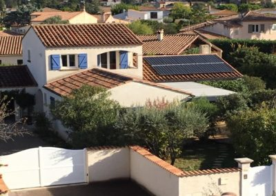 Photo représentant une installation photovoltaïque en autonomie partielle sur une toiture de la maison d'un particulier en PST, où nous voyons un de nos installateurs en train de de peaufiner l'installation des 10 panneaux solaires ALEO P19 ayant une puissance de 300 Wc. Au loin, nous pouvons voir un paysage valloné avec de la verdure, des montages, ainsi que toute sorte d'arbre fleuris. Nous apercevons également un petit chemin en arrière-plan. Cette installation solaire en autoconsommation a été réalisé par l'installateur solaire Libow à Le Vigan courant octobre 2018.