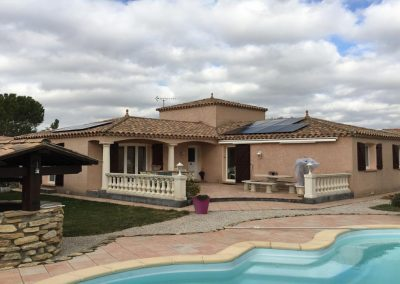 Photo représentant une installation solaire en autoproduction sur la toiture d'une maison d'un particulier en PST, où l'on peut voir 10 modules Q-CELLS 300 installés. Nous voyons que la maison est entourée d'arbres, mais aussi d'autres habitations, et que celle-ci est couverte par de nombreux nuages. Cette installation photovoltaïque en autoconsommation a été réalisé par l'installateur solaire Libow à Montady en février 2019.
