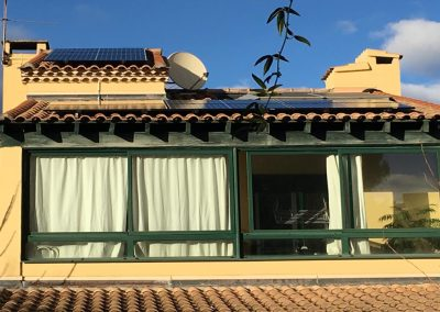 Photo représentant une installation solaire en autoconsommation sur la toiture d'une maison d'un particulier, où l'on peut voir 10 modules DUO-G5 320. Nous pouvons voir que la maison est entourée de verdures, notamment des arbres et nous voyons également un ciel dégagé malgré quelques petits nuages. Cette installation solaire en autonomie partielle a été réalisé par l'installeur solaire Libow à Grabels en février 2019
