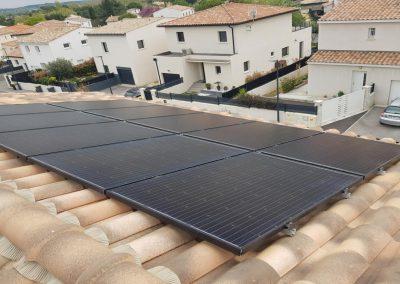 Photo représentant de nombreux panneaux solaires en autonomie partielle sur la toiture d'une maison, comprenant notamment 8 panneaux photovoltaïques, tous posés avec la technique en surimposition. Ces modules solaires sont des Q.CELLS G5-DUO avec une puissance de 320 Wc chacun. Au loin, nous pouvons apercevoir de nombreux arbres, ainsi que des maisons voisines, mais également de la verdure à côté de la maison. On aperçoit également des poteaux électriques en arrière-plan. Cette installation solaire en autonomie partielle a été réalisé par l'installateur solaire Libow à Marcorignan en février 2019.