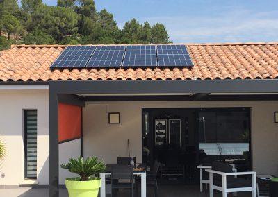 Photo représentant une installation photovoltaïque sur une toiture de la maison d'un particulier, où l'on peut voir 8 modules posés en tout . Les modules solaires posés sont des Q.CELLS d'une puissance de 315 Wc chacun. Derrière maison d'un style moderne, nous pouvons apercevoir des pins, végétation typique de la région Occitanie. .