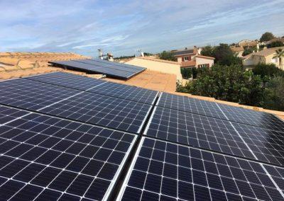 Photo représentant une installation en autoconsommation sur la toiture d'une maison d'un particulier à Maugio (34150), où l'on peut voir clairement 6 modules posés sur 9 en tout . Les panneaux solaires posés sont des Q-CELLS d'une puissance de 325 Wc chacun. Nous pouvons apercevoir en arrière plan un ciel clair ainsi que de nombreuses maisons.