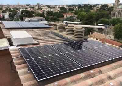 Photo représentant une installation solaire photovoltaïque sur une toiture de la maison d'un particulier , où l'on peut voir 9 modules posés en tout . Les modules solaires posés sont des Q.CELLS. Derrière cette maison, on peut apercevoir une église de montpellier