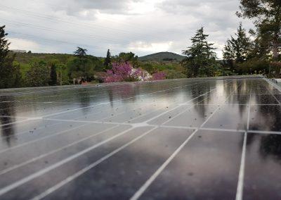 Photo représentant une installation solaire photovoltaïque sur une toiture de la maison d'un particulier , où l'on peut voir 10 modules posés en tout . Les modules solaires posés sont des Q.CELLS d'une puissance de 300 Wc chacun, avec le cadre noir. Cette maison du sud de la France est aujourd'hui sous un temps pluvieux. Cependant, cela n'enlève rien au charme qui s'en dégage grâce à la verdure environnante.